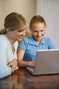 Caucasian mid-adult woman and pre-teen girl using laptop comput